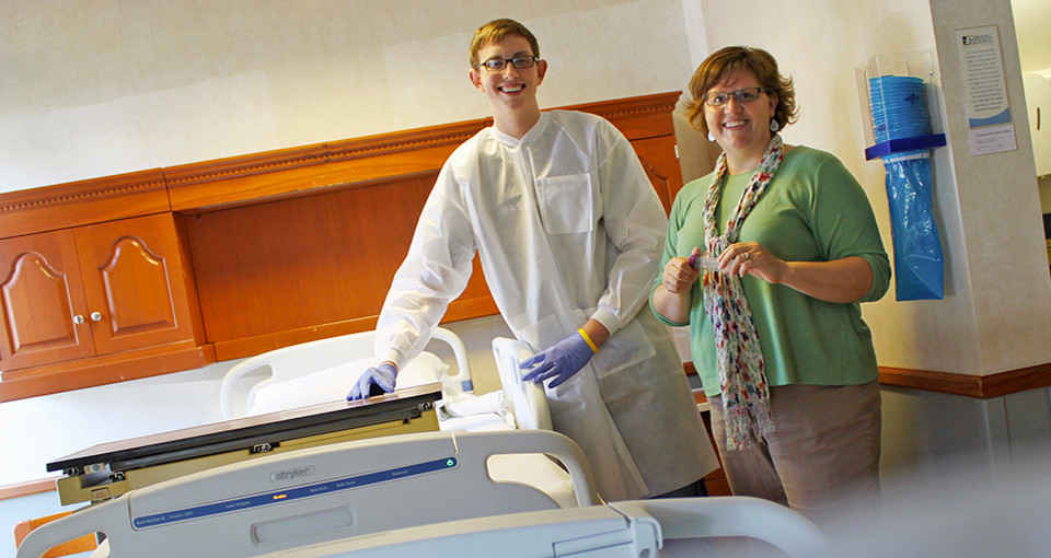 Two students from Grinnell College posing in a hospital room.