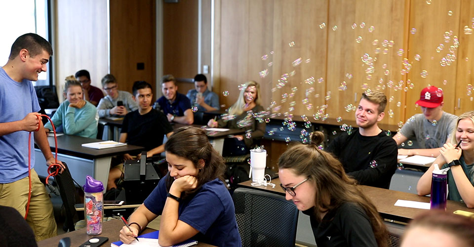 students react to a bubble machine used during a class demonstration