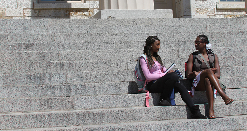 Two female African American students sitting on the steps of the Old Capitol