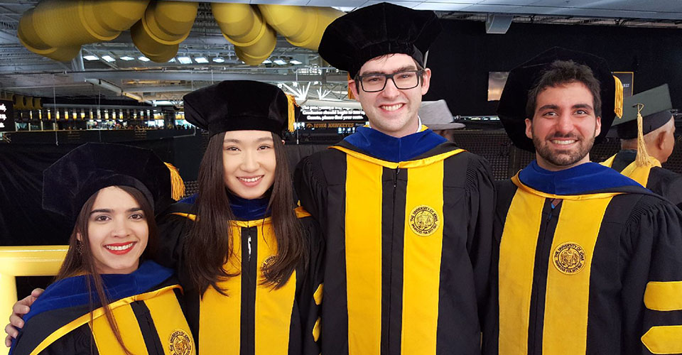 Four PhD recipients posing at the 2017 graduation ceremony