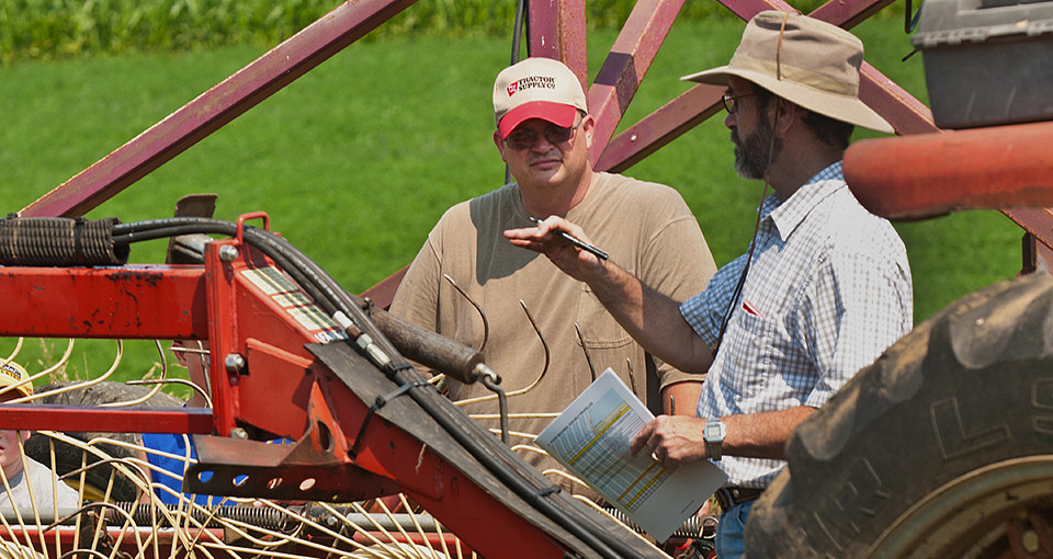 Photo of a researcher speaking with a farmer near a hay baler