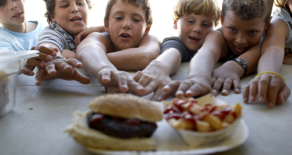 Children (6-10) at fastfood vendor's window, reaching for plate of fries and hamburger