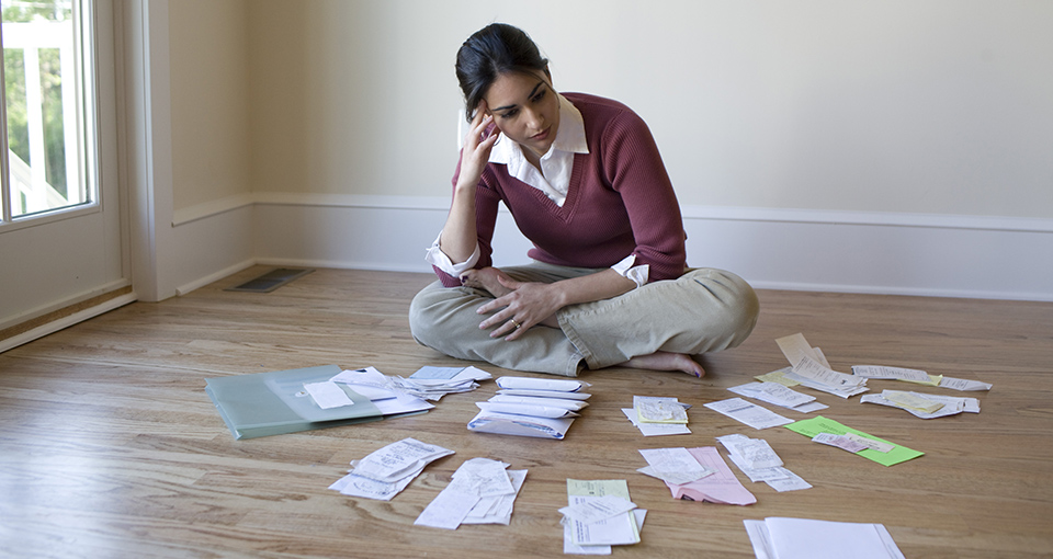 financial stressors slider - Woman looking at bills and receipts on floor