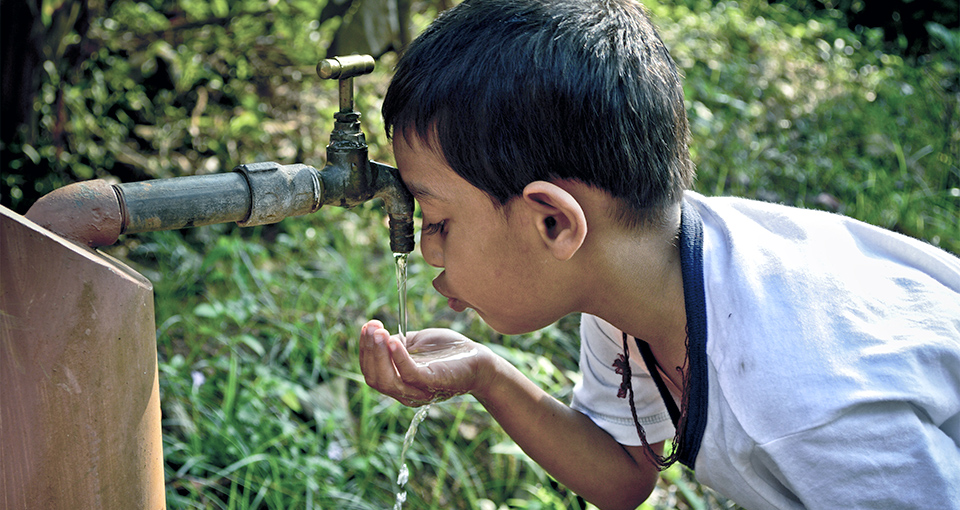 young boy drinking from an outdoor water tap