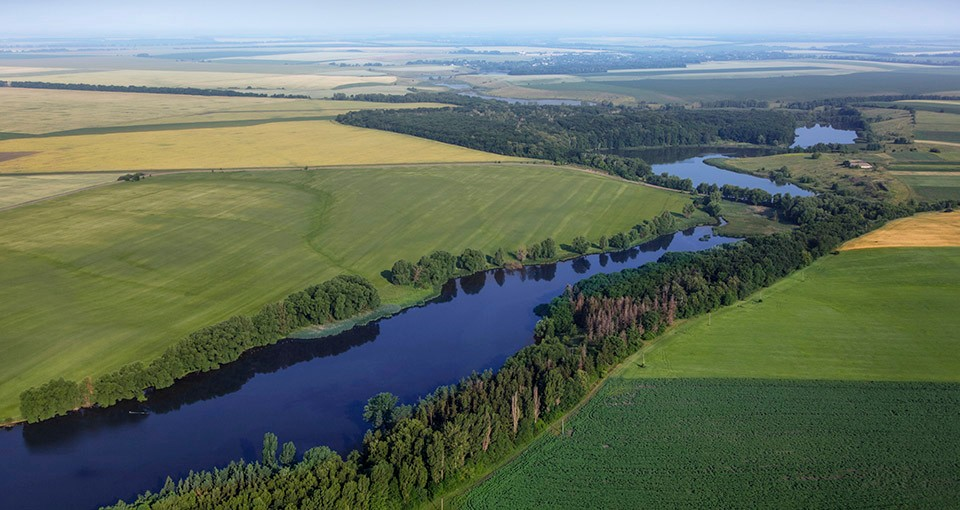 Photo of an aerial view above green fields and a river