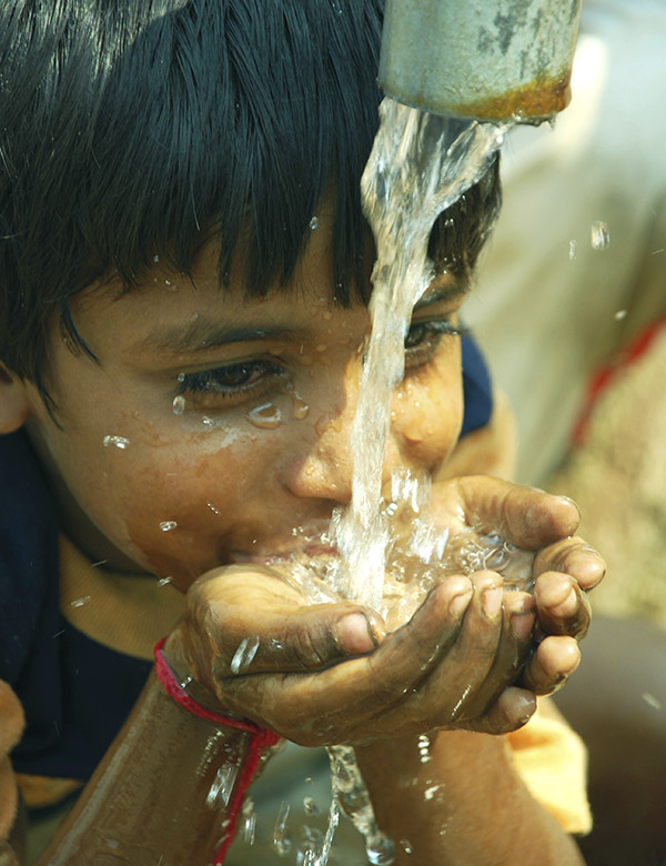 A child drinks water from a running pipe.
