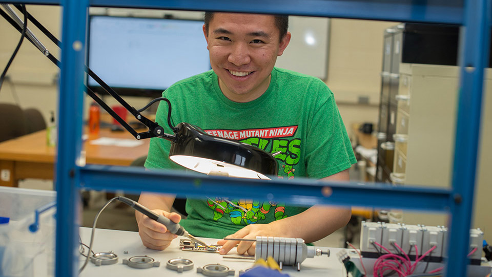 Photo of a student with a soldering iron working in a lab
