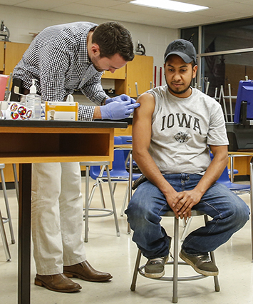 University of Iowa third year medical student Brian Guetschow gives a flu shot to Jose Santos of West Liberty