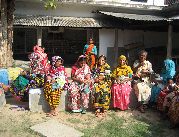 Women with their infants sitting outside in Bangladesh