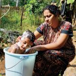 Mother washes boy in bucket.