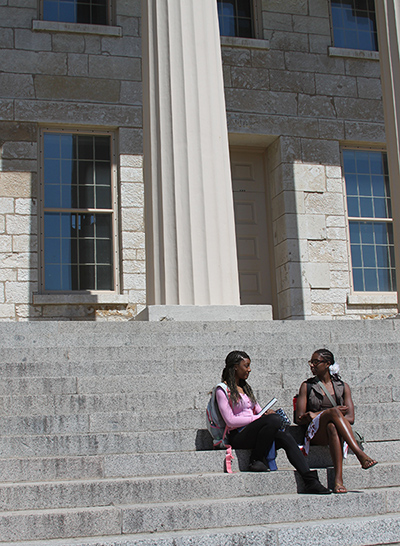 Students sit on the steps of the Old Capitol on the University of Iowa campus.