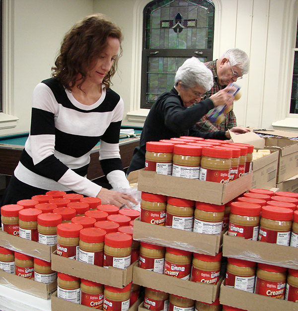 Volunteers prepare food for Carry On Bags