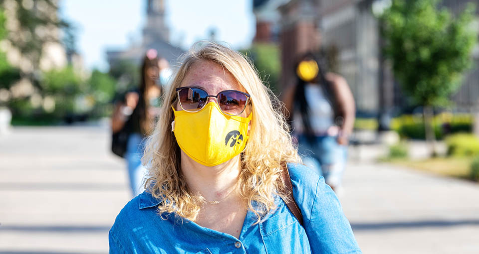 Young woman wearing a Hawkeye face mask on campus