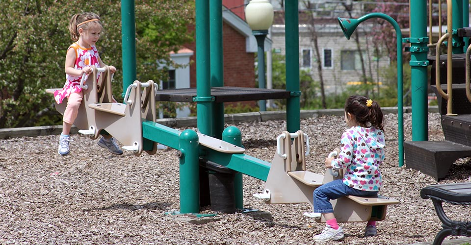 two girls play at a neighborhood park