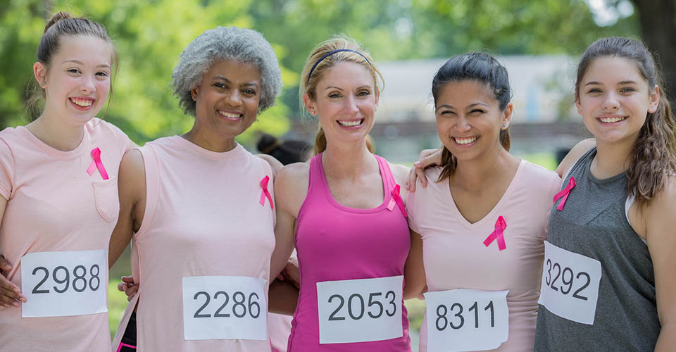 Diverse team of women smile before running in charity marathon for breast cancer research.
