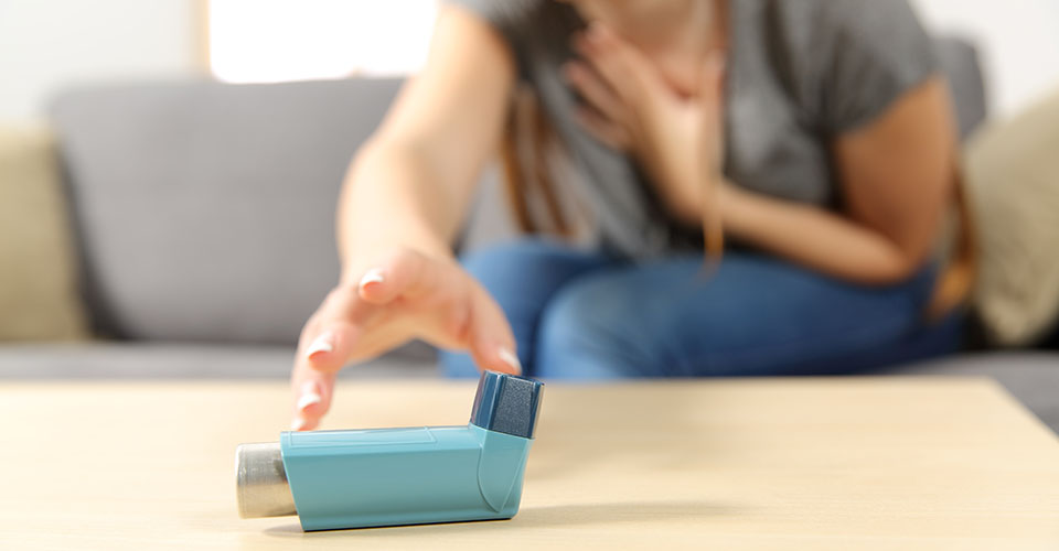 Girl suffering asthma attack reaching inhaler