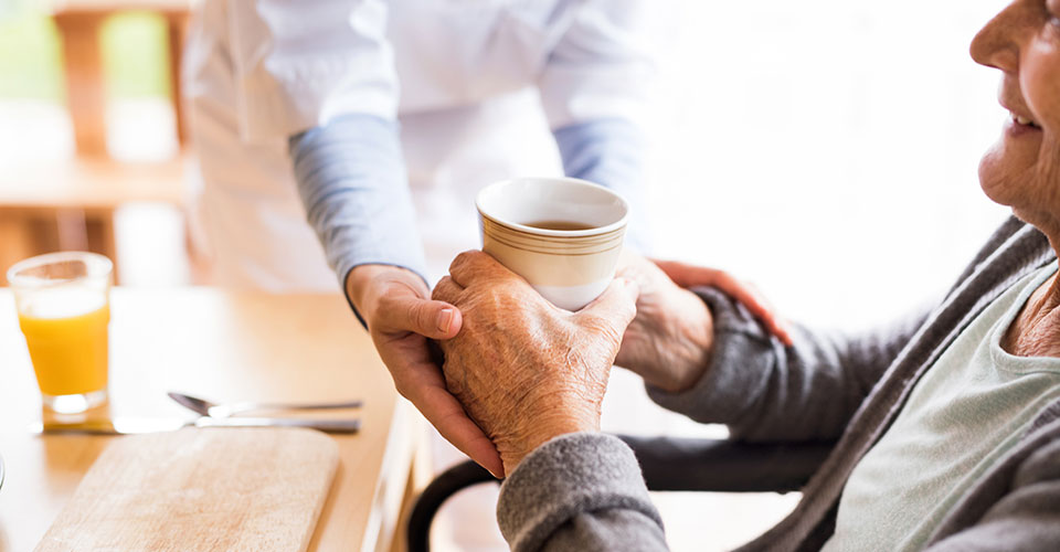 a caregiver hands a cup to an elderly person