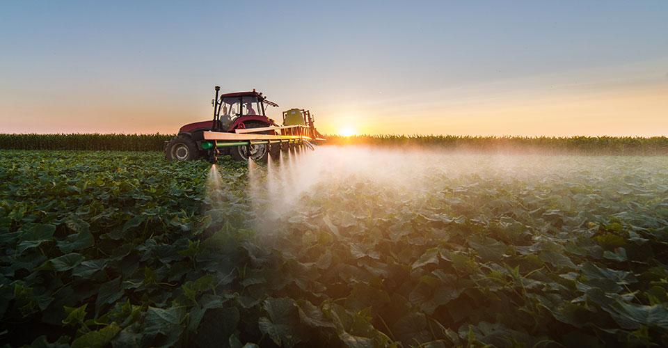 a tractor spraying a field with pesticide