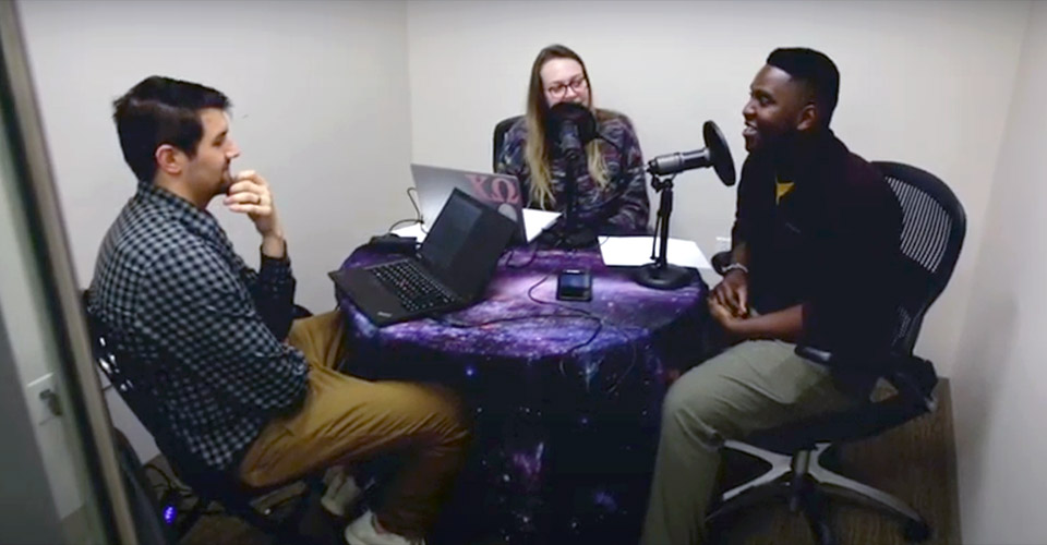 three students working on a podcast