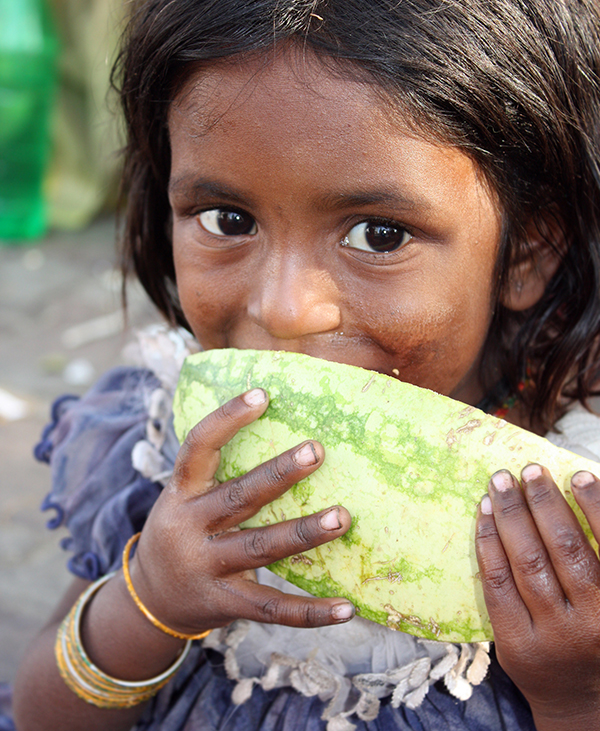 A girl in India eating watermelon.