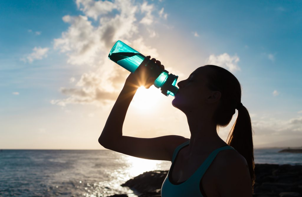 Young woman drinking from water bottle on beach