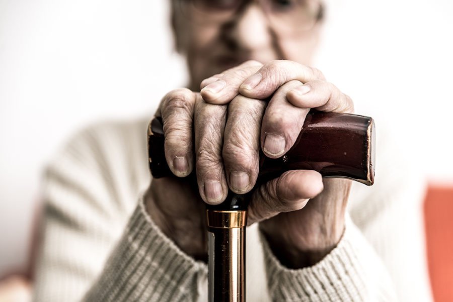 close up of elderly hands on a cane