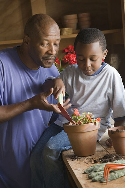 Boy gardening with the help of his grandfather