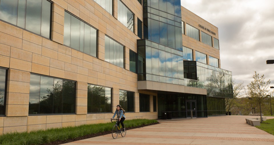 A cyclist rides on the south patio of the College of Public Health Building.
