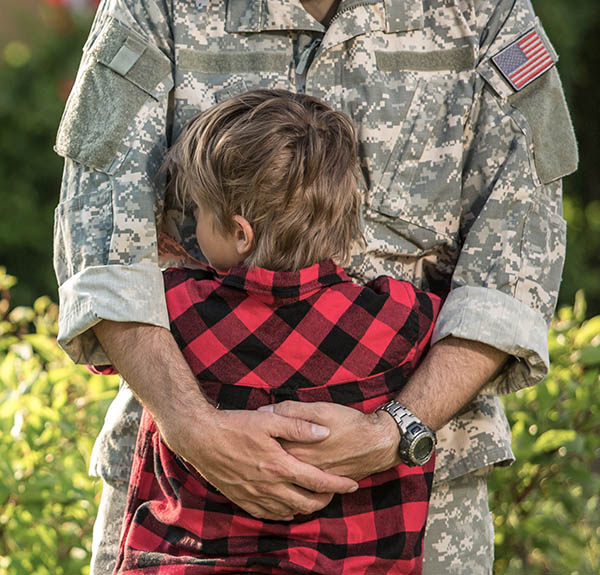 a soldier hugging his child