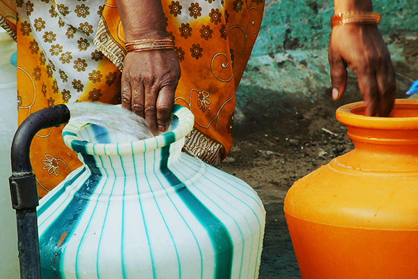 photo of a woman collecting water in plastic pots