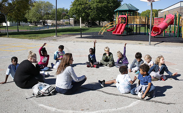 a group of elementary kids sit in a circle on the playground