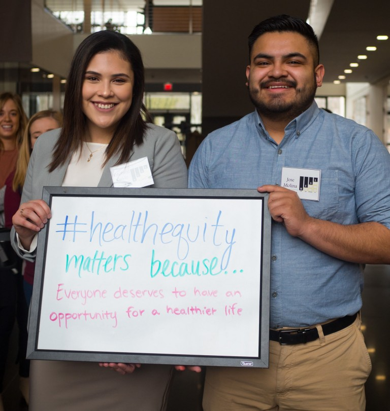 "Estefany Guido and Jose Molina hold up a sign reading ""#healthequitymatters because... Everyone deserves to have an opportunity for a healthier life."""