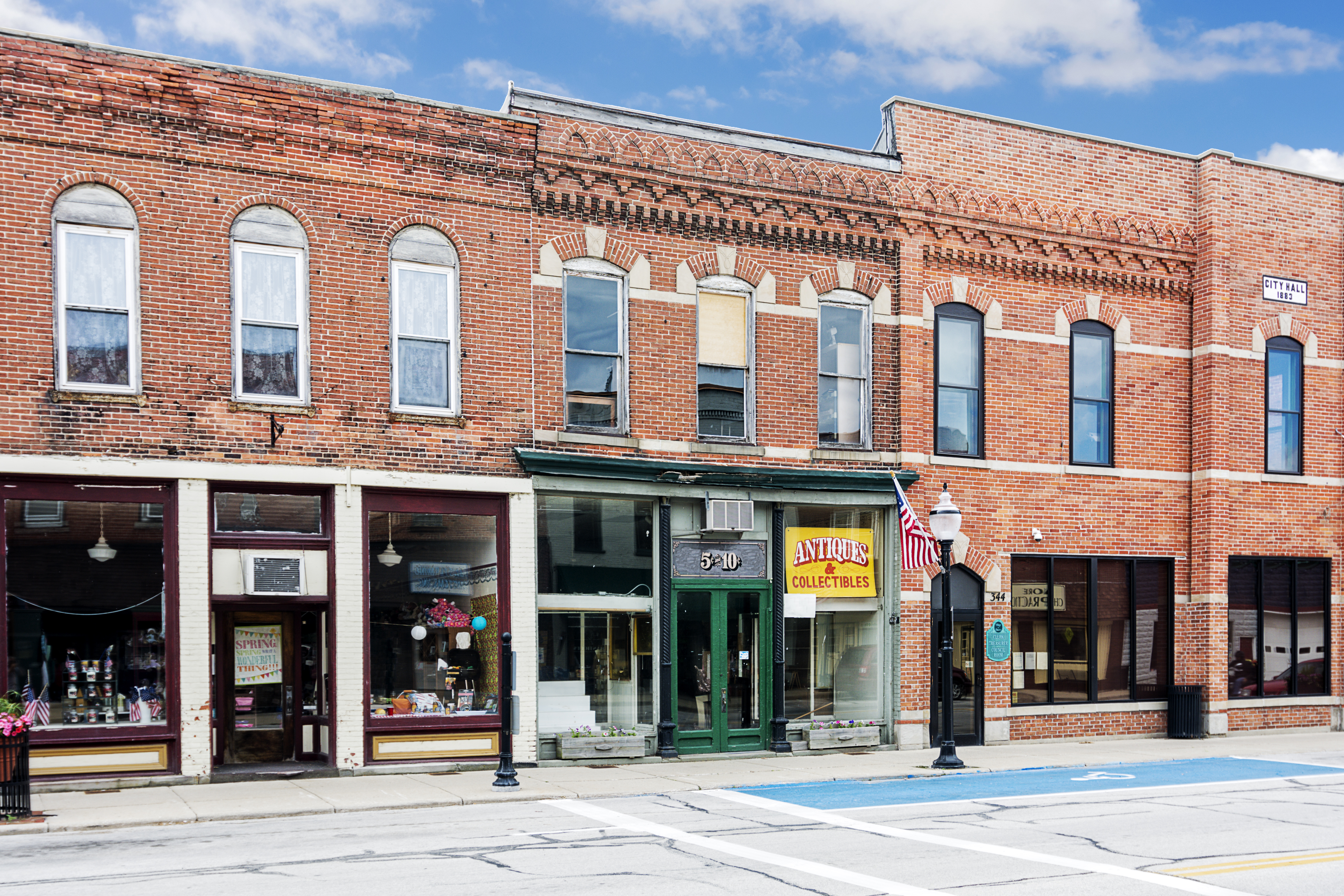 A photo of a typical small town main street in the United States of America. Features old brick buildings with specialty shops and restaurants including an old five and dime store. Decorated with spring flowers and American flags.