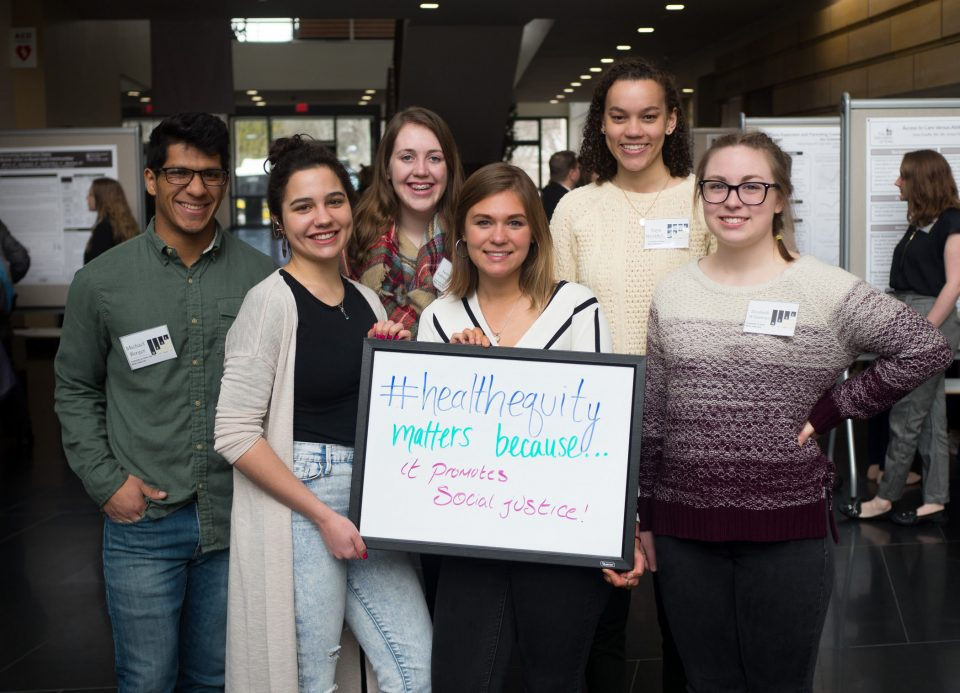 """Students hold up sign saying """"#healthequitymatters because it promotes social justice."""""""
