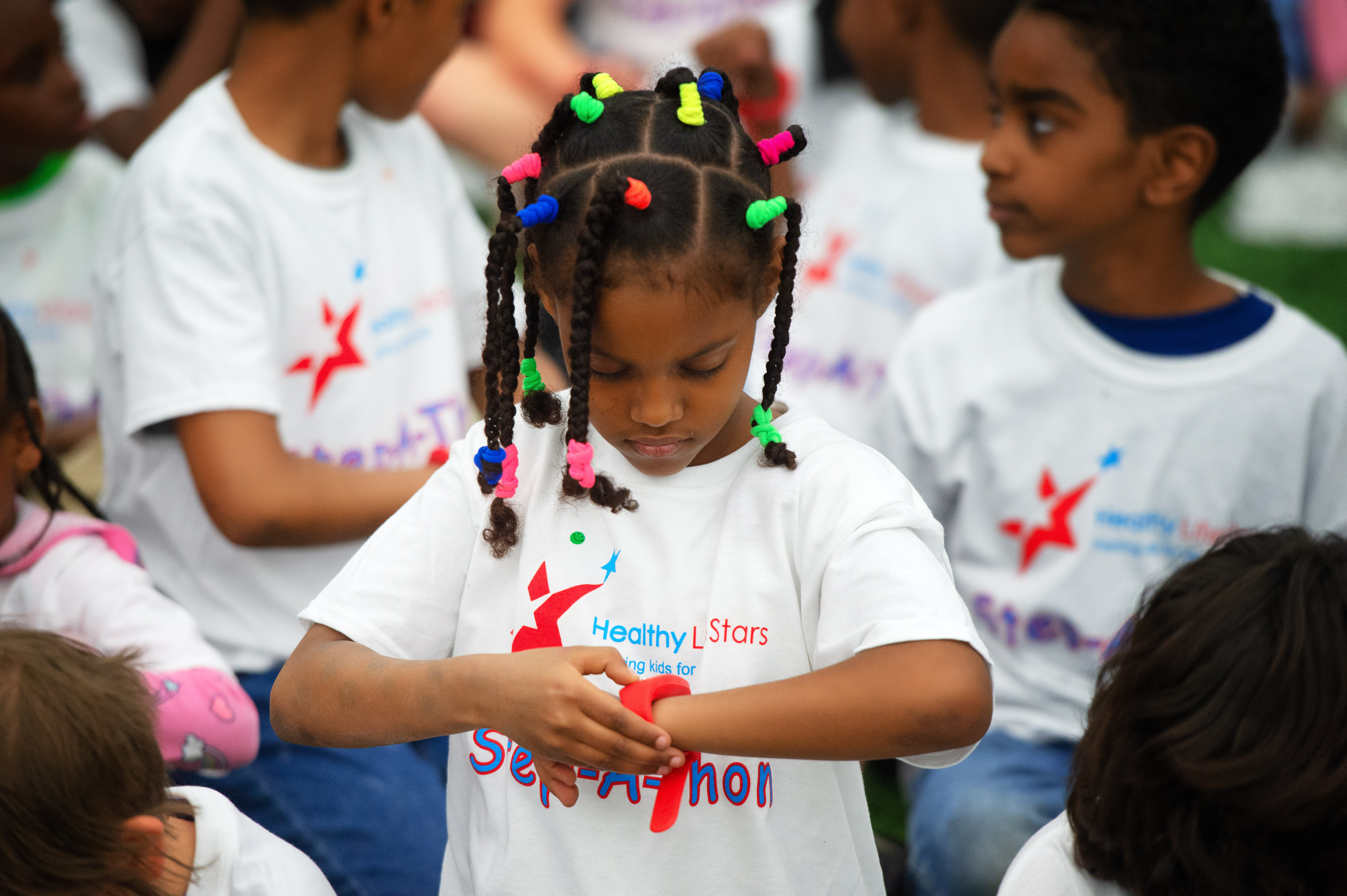 A child checks her wrist band and the Healthy LifeStars event