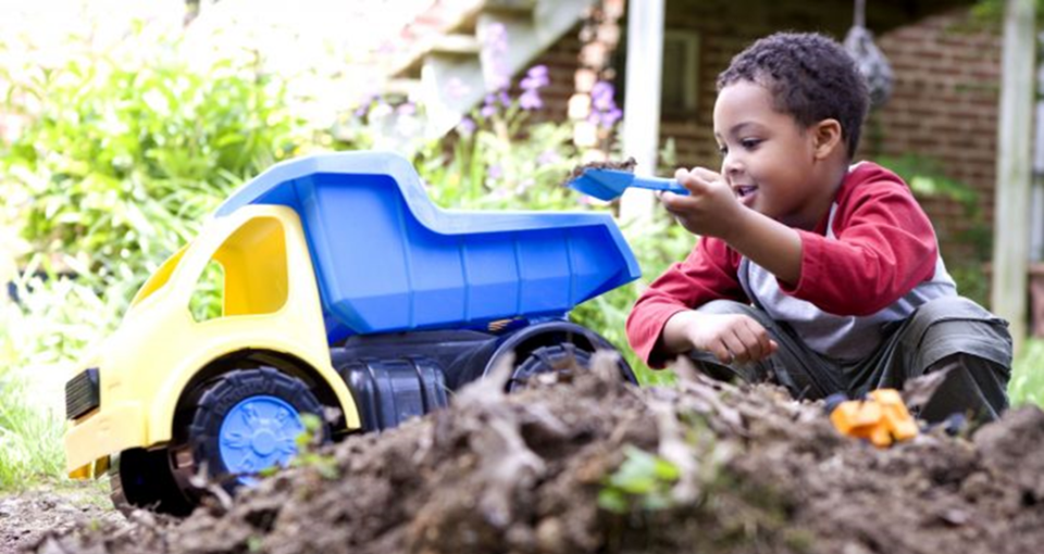 Little boy playing with toy dump truck in the dirt