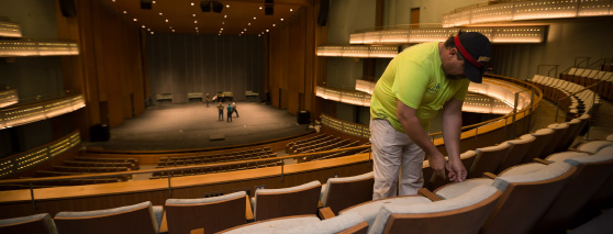 a worker tends to a seat in Hancher Auditorium
