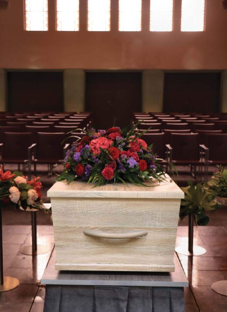 a casket topped with flowers in an empty funeral home