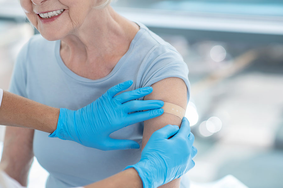 an older woman receives a bandage on her arm after a vaccine