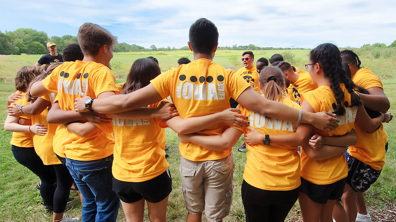 UI students in a huddle during a teambuilding exercise