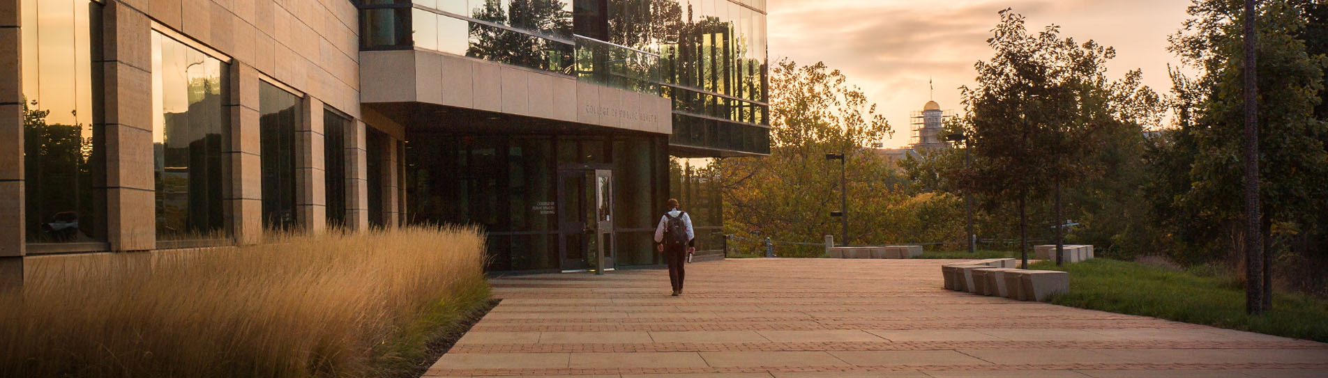 Student walking into the College of Public Health Building at dawn.