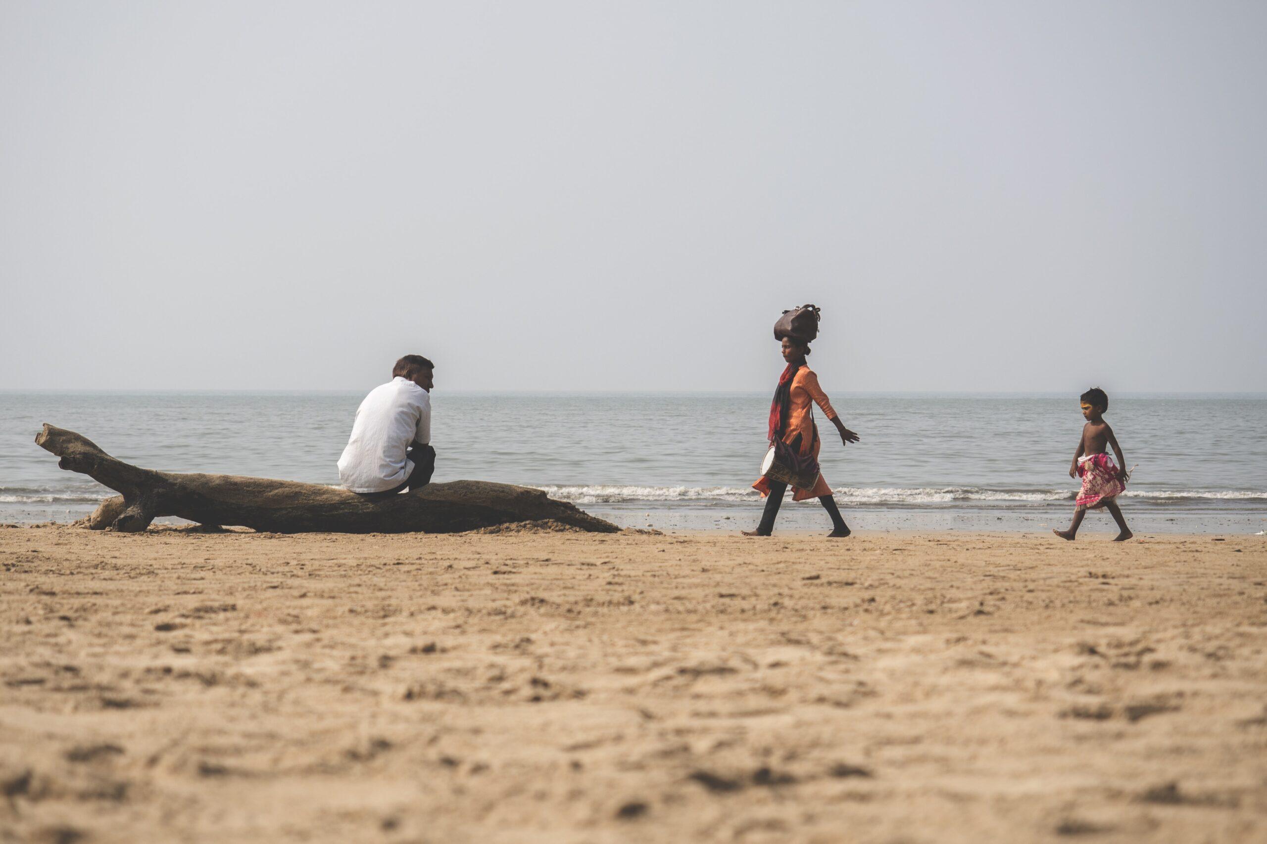 People walking along beach in India