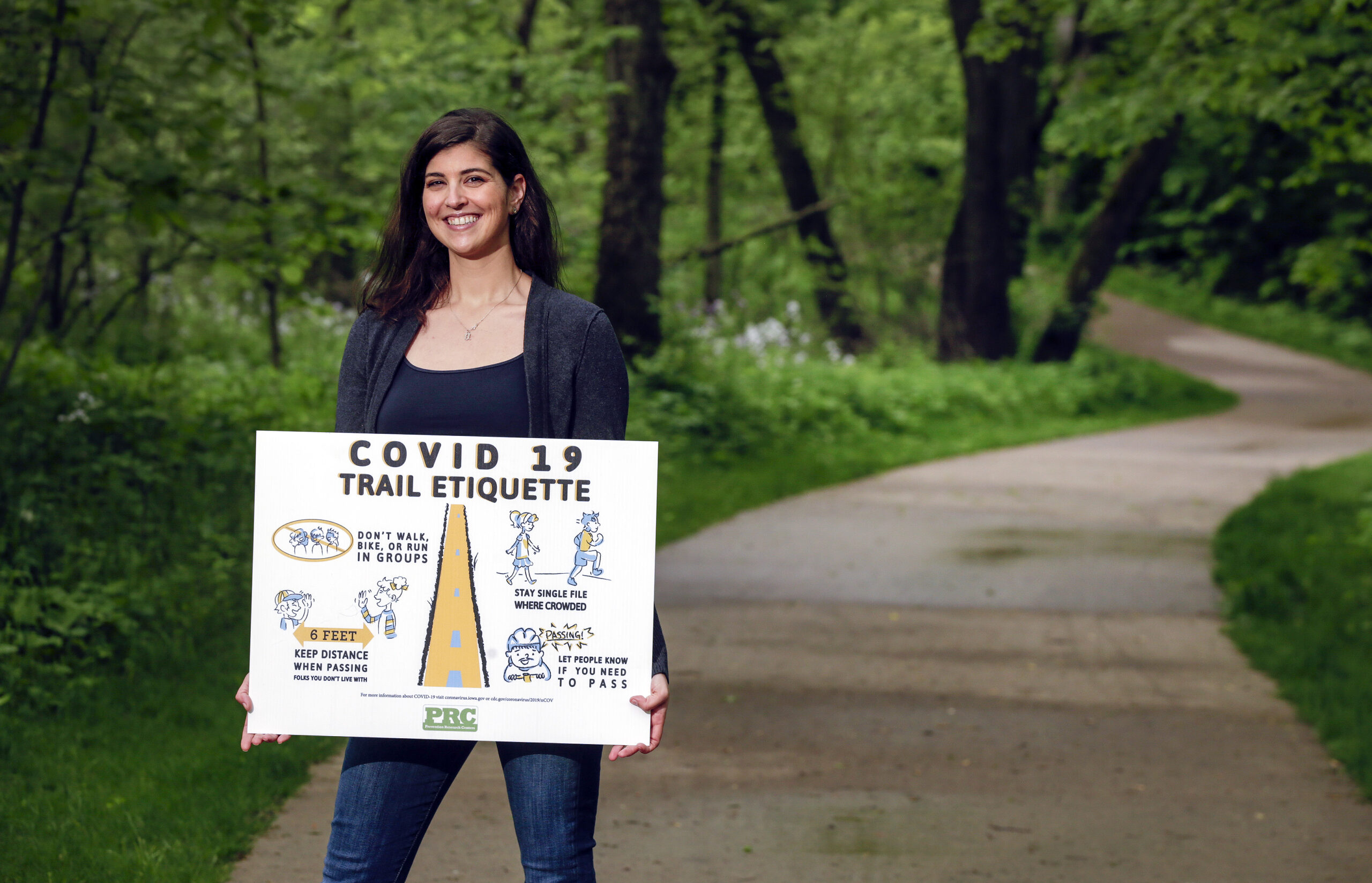 CPH student Anne Abbott posing with a COVID-19 trail etiquette sign she created.