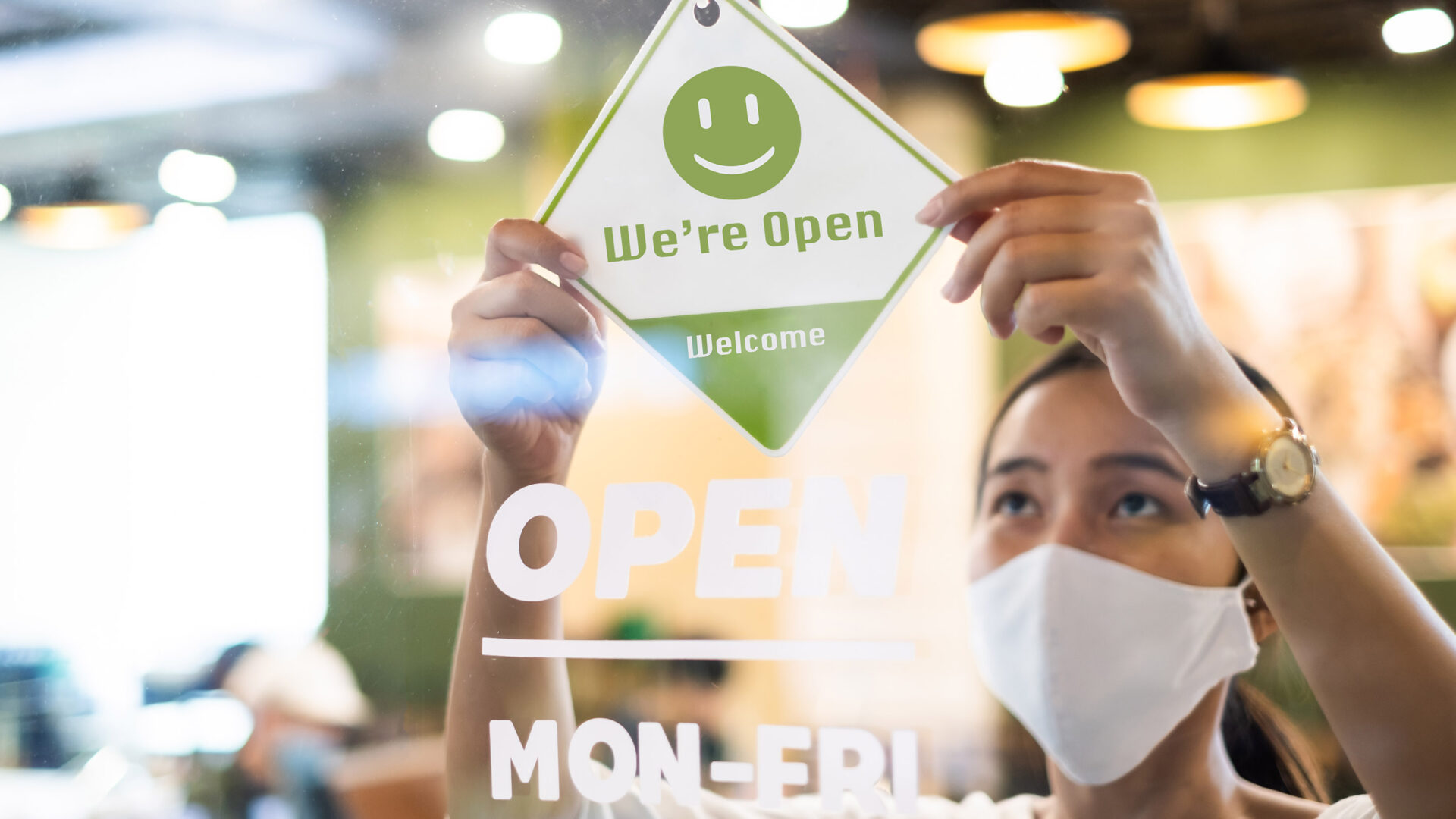 A woman wearing a mask hangs an open sign on the door of a cafe