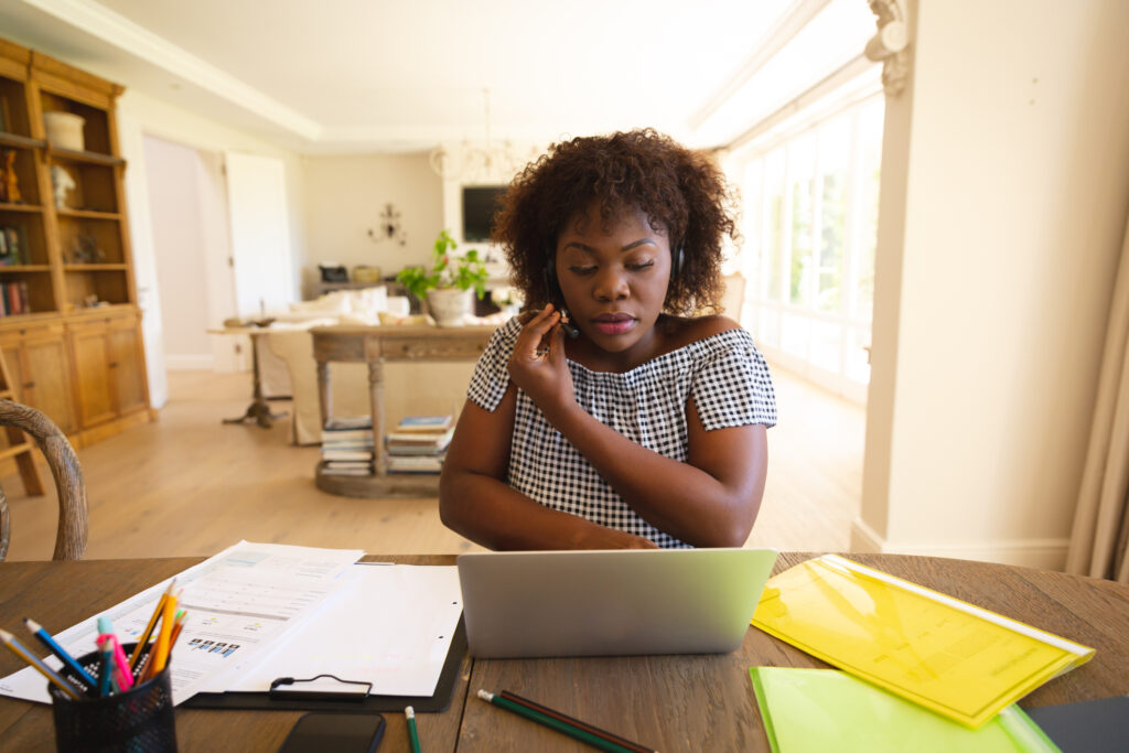 A woman working from home on a laptop and phone
