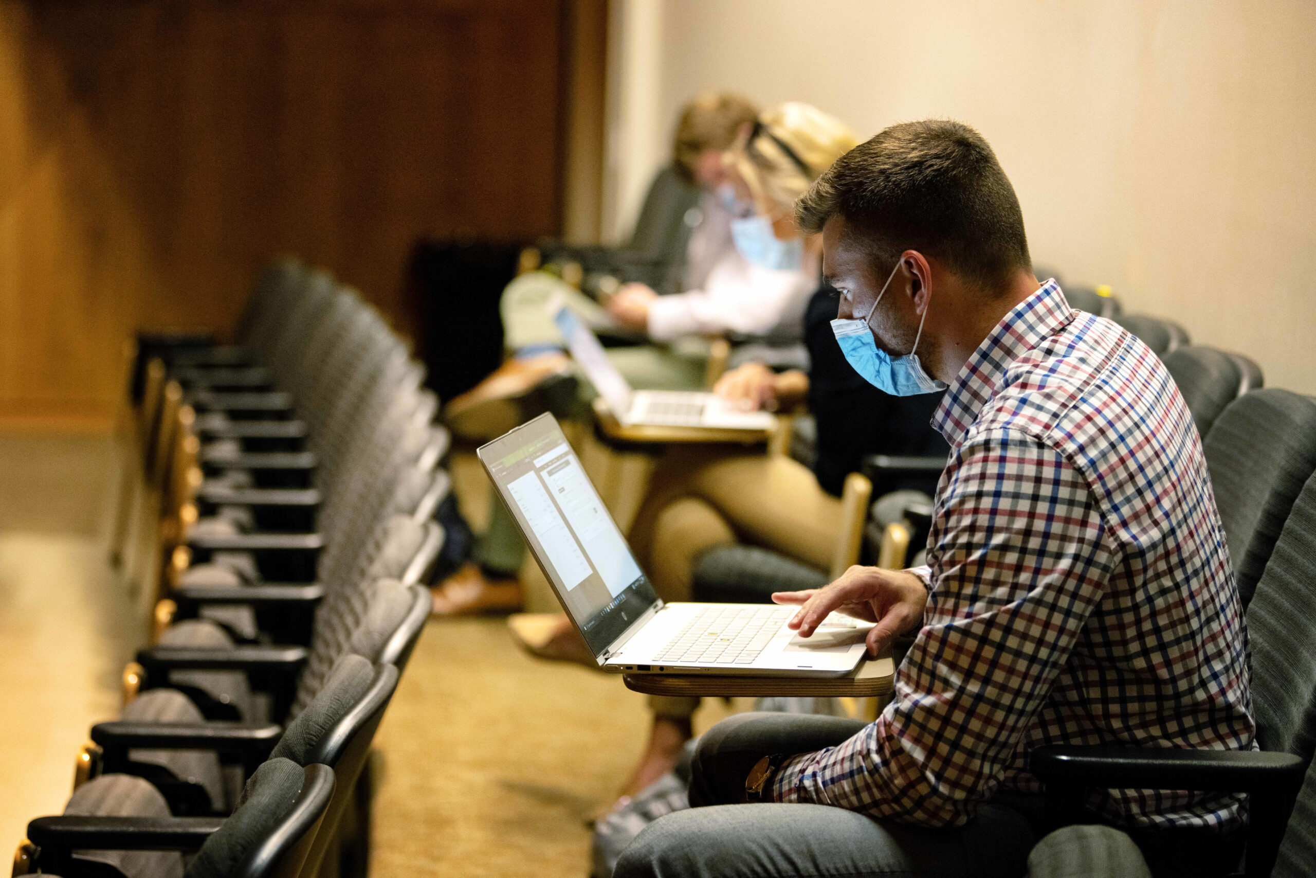 A CPH student with a laptop listens to a lecture in Callaghan Auditorium on the first day of classes.